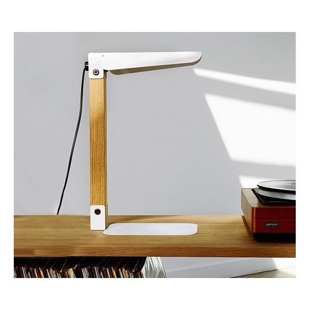 Lámpara de sobremesa Merlin en color blanco apoyada en una mesa de perfil marca ethnicraft